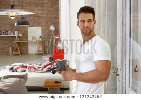 Handsome young man looking out of window, holding tea mug.