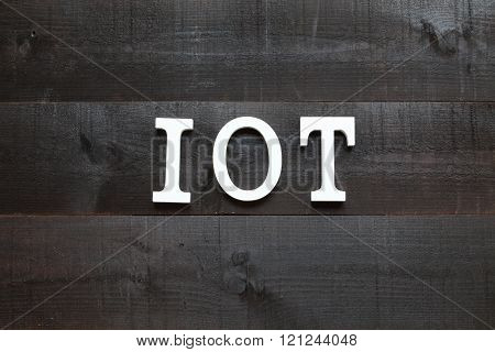 The acronym IOT Internet of things on dark background