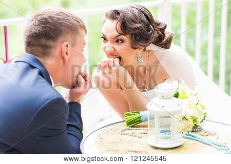 Cheerful young couple in love having fun outdoors. Bride and groom posing. Emotional faces of people