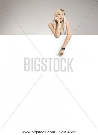 Attractive blond beauty over white board, lots of copyspace