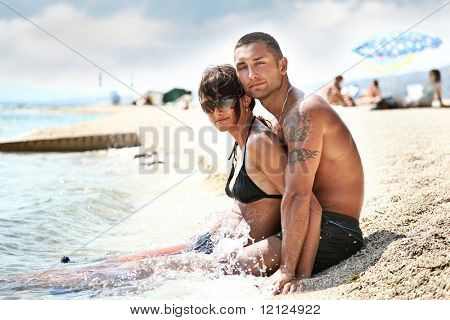 Attractive couple relaxing on the beach