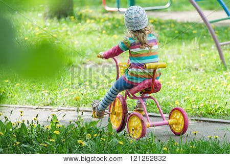 Back view full length portrait of preschooler girl riding kids pink and yellow tricycle on playgroun