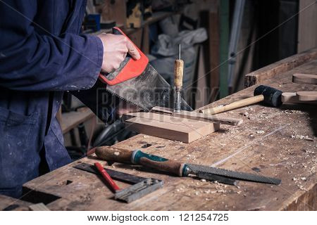 Carpenter Sawing A Piece Of Wood With A Handsaw