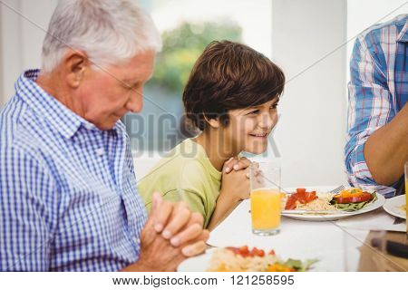 Family sitting at dining table and praying together before meal