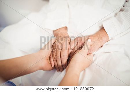 Close-up of senior woman and nurse holding hands