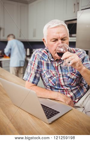 Senior man drinking red wine while using laptop and woman working in kitchen behind him