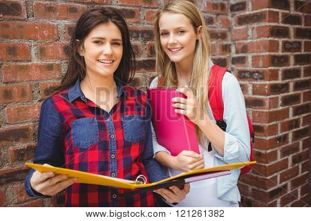 Smiling students with binder looking at camera at university
