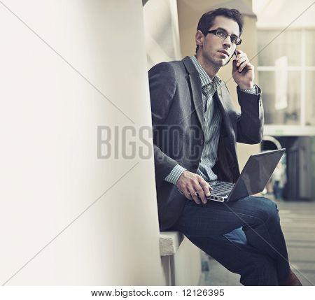 Empresário bonitão falando sobre celular