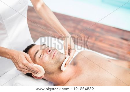 Man receiving a facial massage from masseur in spa