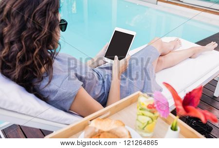Young woman relaxing on a sun lounger and using a digital tablet near poolside