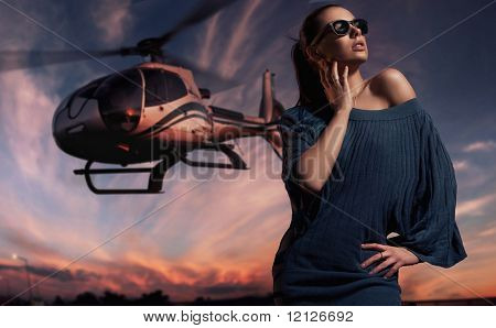 fashionable lady wearing sunglasses with helicopter in the background