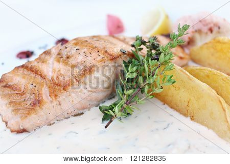 Baked salmon with potato slices, and thyme sauce. Close-up.
