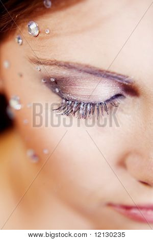 Beautiful half face with make-up and sparkles. Shallow DOF, focus on the eye.