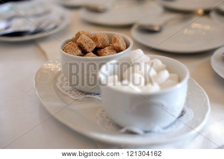 Brown and white sugar pieces on the table.
