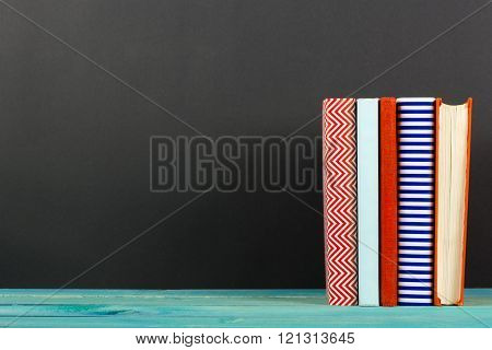 Composition with old vintage colorful hardback books, diary on wooden background