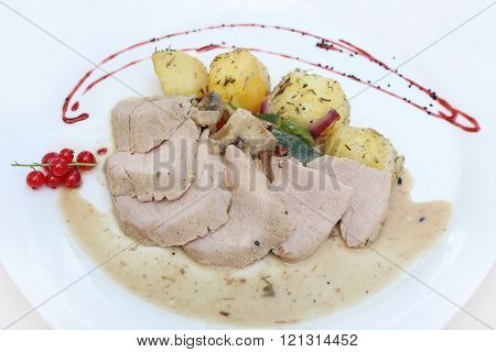 Baked pork with potatoes, vegetables, gravy and currant sauce
