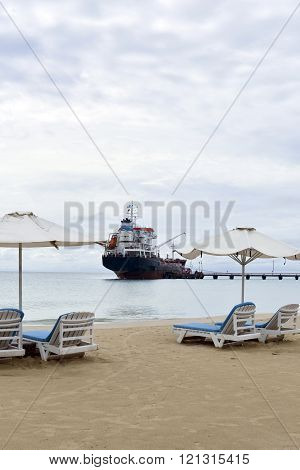 oil tanker ship on Picnic Center Beach Big Corn Island Nicaragua with beach chair lounges and umbrellas