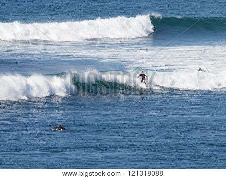Surfers Ride The Waves