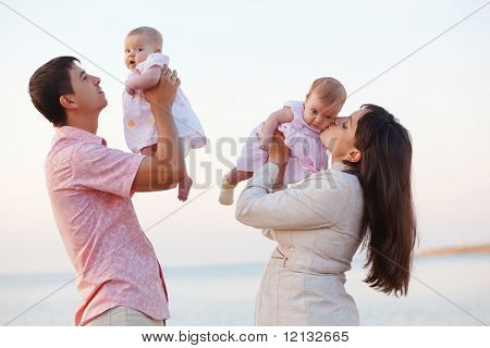 Young parents with children kissing over sea