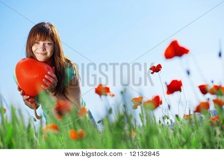 Happy teenage girl holding heart in poppies field