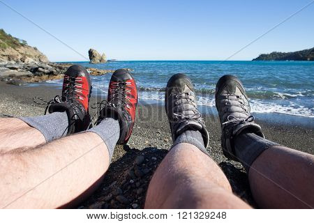 Camping people putting on hiking shoes by tent.
