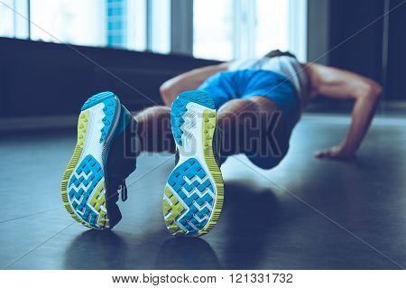 Perfect push-up. Rear view of young man in sportswear doing push-up at gym