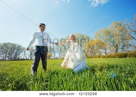 Bride and groom walking at filed on fresh green grass