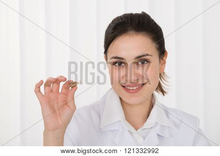Female Doctor Holding Hearing Aid