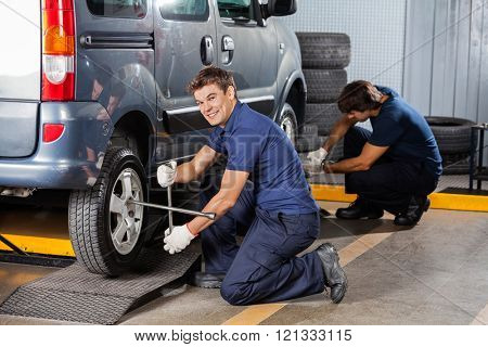 Happy Mechanic Fixing Car Tire At Repair Shop poster