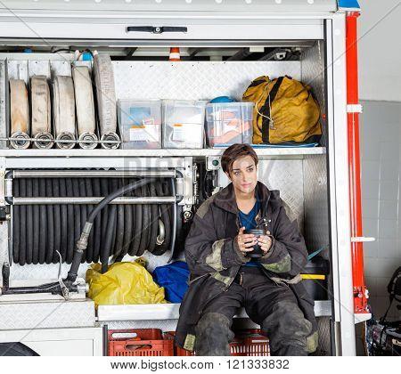 Thoughtful Firewoman Holding Coffee Mug In Truck