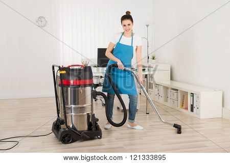 Female Janitor Cleaning Floor With Vacuum Cleaner