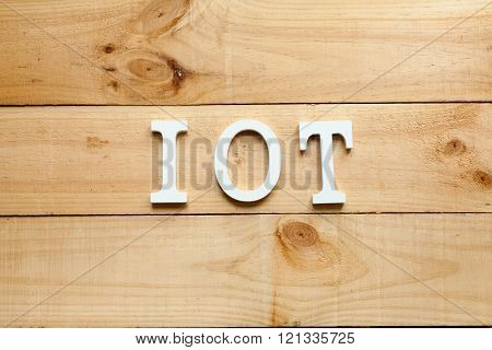 The acronym IOT Internet of things on wooden background