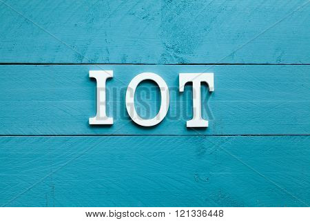 The acronym IOT Internet of things on blue background