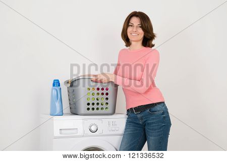 Young Woman Standing By Washing Machine