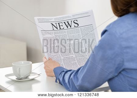 Businesswoman Reading Newspaper In Office