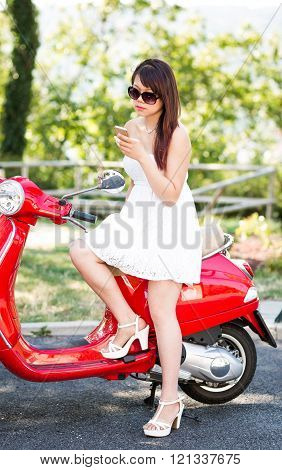 Portrait Of Happy Young Woman With Smartphone On The Red Scooter. Defocused Background.