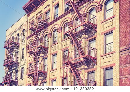 Old film retro toned photo of New York building with fire escape ladders, USA.