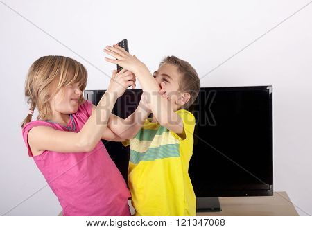 Girl and boy siblings fighting over the remote control in front of the television