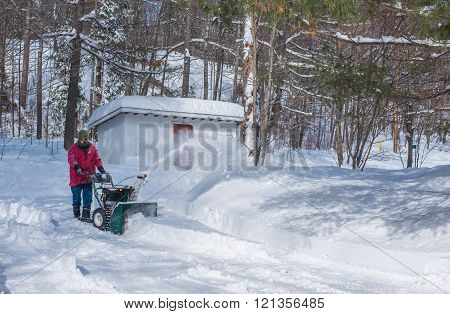 A man operating a snow thrower on a winter day in Canada.