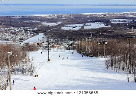 COLLINGWOOD, ONTARIO - JAN 22,2016. A view from top of the slope to the village and bay below. Also some people are enjoying themselves skiing and some taking a ride on the chair lift.