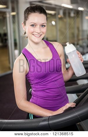 Smiling woman holding bottle of water in the gym
