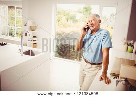 Smiling senior man on a phone call in the kitchen
