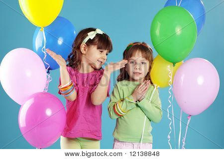 Happy children with colorful air balloons over blue