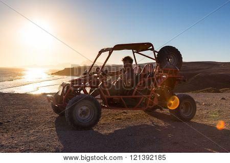 Man driving quadbike in sunset.