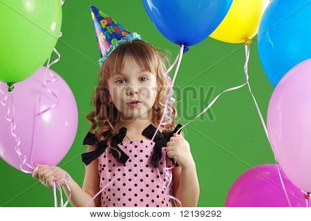 Child celebrating birthday on green studio background