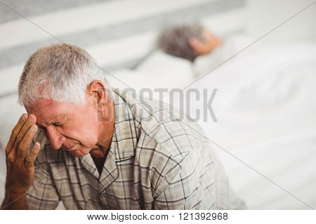 Senior man in bedroom suffering from headache
