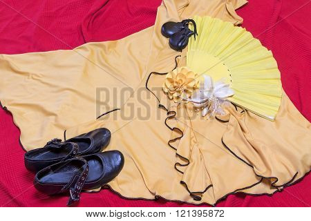 Yellow clothing for Flamenco dance. Black shoes, paper rose and castanets are lying on a red underlay.