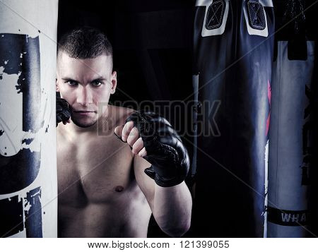 Young fighter standing in a fighting stance on black background