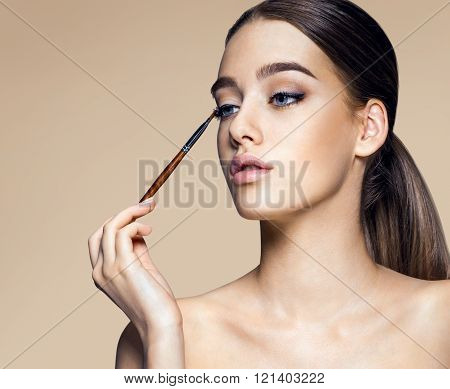 Enchanting young girl with brush for eyeshadow