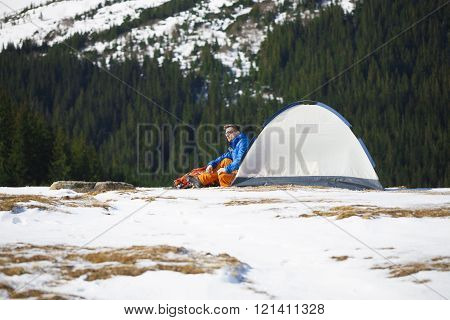 Tourist Sitting Near A Tent And A Backpack.